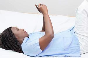 Young woman lying on the bed using a mobile phone