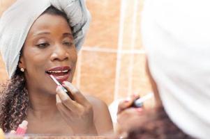 Beautiful woman applying makeup in the bathroom
