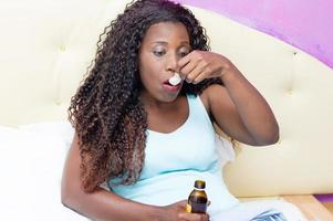 Sick African woman drinking medicine in bed