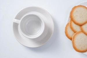 Taza de café vacía con galletas sobre fondo blanco.