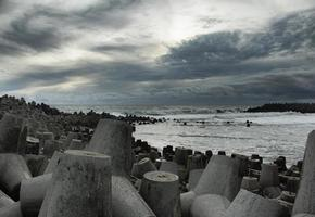 Seaside view with huge rocks and a wave photo