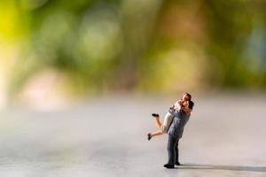 Miniature bride and groom outdoors with a green bokeh background
