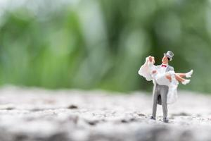 Miniature bride and groom standing outdoors with a blurry nature background