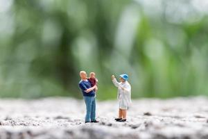 Miniature parents with a child walking outdoors on a blurry nature background, happy family concept