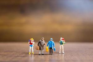 Miniature travelers standing on a wooden background, travel concept