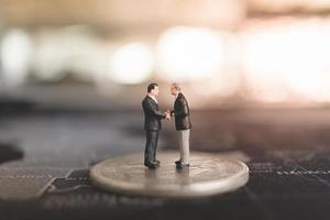 Miniature businessmen standing on a coin, business and finance concept