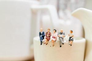 empresarios en miniatura sentados en una taza de té foto