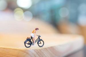 Miniature person cycling on a wooden bridge, health care concept
