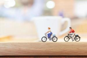 Miniature people cycling on a wooden bridge, health care concept
