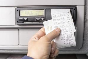 Digital tachograph and drivers hand holding print with driving times of the day photo