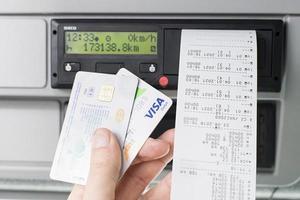 Olomouc, Czech Republic 2021- Hand holding a driver digital card, bank debit card and digital tachograph print out in front of a digital tachograph photo