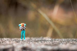 Miniature backpacker standing on a concrete floor with a bokeh nature background