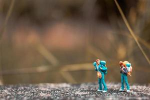 Miniature backpackers standing on a concrete floor with a bokeh nature background photo