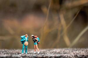 Mochileros en miniatura de pie sobre un piso de concreto con un fondo de naturaleza bokeh foto
