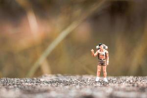 Miniature backpacker standing on a concrete floor with a bokeh nature background photo