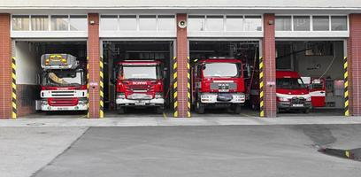 Prostejov, Czech Republic 2017- Red fire fighter trucks parked in open garage of the fire brigade photo