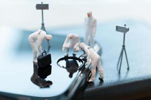 Policía en miniatura y detectives que trabajan en un teléfono inteligente, investigación de la escena del crimen y concepto de ciberdelito foto
