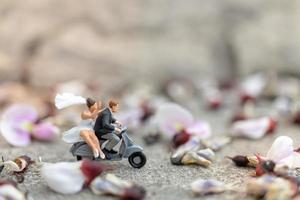 Miniature couple riding a motorcycle in a garden photo