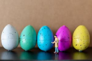 Miniature artist holding a brush and painting Easter eggs for Easter