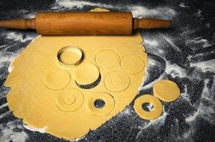 Dough being cut for doughnuts photo