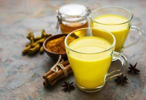 Golden milk with cinnamon, turmeric, ginger and honey over concrete background