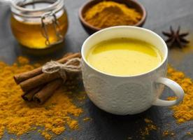 Golden milk with cinnamon, turmeric, ginger and honey over black concrete background