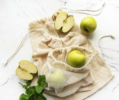 Fresh green apples in mesh bags, top view