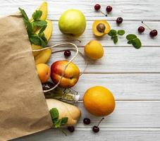 Healthy food in paper bag, fruits and berries photo