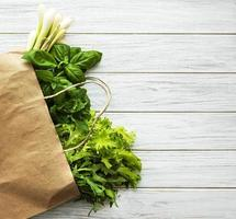 Fresh greens in a paper bag on a wooden background