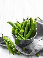 Fresh green peas in a small metal bucket on old wooden background