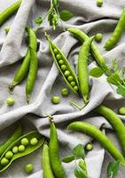 Pods of green peas with pea leaves on a fabric background