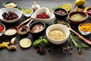 Various spices in a bowls on a black concrete background photo