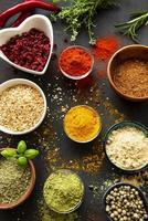 Colorful and aromatic herbs and spices on a dark background photo