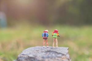 Miniature travelers with backpacks walking in the wild, travel and adventure concept photo