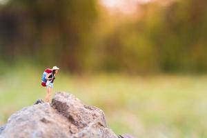 Miniature traveler with a backpack walking in the wild, travel and adventure concept photo