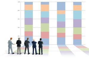 Empresarios en miniatura de pie con gráficos sobre un fondo blanco. foto