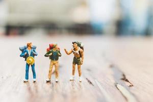 Turistas mochileros en miniatura gente de pie sobre un fondo borroso de madera foto