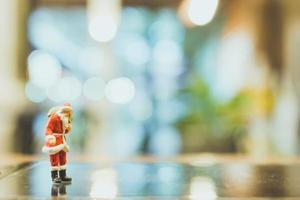 Miniature Santa Claus standing on glass with a blurred background