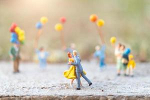 Miniature couple dancing with people holding balloons in the background