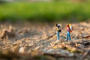 Miniature travelers with backpacks walking in a meadow, travel and adventure concept photo