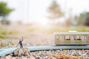 Miniature railway staff working at a railway, travel by train concept photo