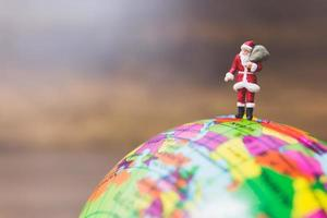 Miniature Santa Claus carrying gifts standing on a globe