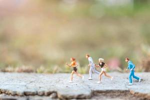 Miniature people running on a road with a nature background, health and lifestyle concept photo