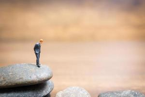 Miniature businessman standing on a stone, challenges and risks concept photo