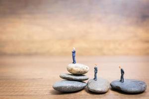 Miniature businessmen standing on a stone, challenges and risks concept photo