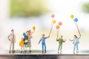 Miniature family with balloons, happy family relations and carefree leisure time concept