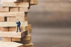 Miniature businessman standing on woodblocks