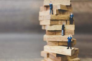 Miniature businessmen standing on woodblocks