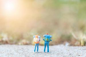 Miniature travelers with backpacks standing on a road, travel and adventure concept photo