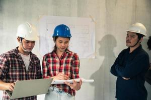 Young Asian couple in hard hats examining house plans with engineer